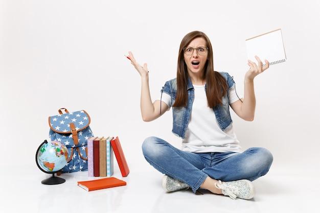 Młoda zirytowana studentka w okularach rozkładająca ręce trzymająca ołówek, notatnik siedzący w pobliżu kuli ziemskiej, plecak, podręczniki szkolne na białym tle