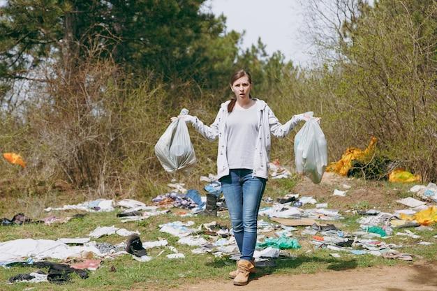 Młoda zirytowana zdenerwowana kobieta w zwykłych ubraniach czyści, trzymając worki na śmieci i rozkładając ręce w zaśmieconym parku