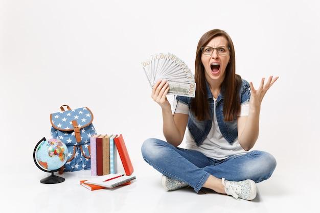Młoda zła studentka krzyczy rozkładając ręce trzymając pakiet wiele dolarów, pieniądze w gotówce siedzą w pobliżu plecaka na świecie, książki na białym tle