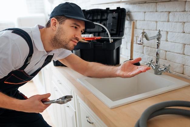 Młoda złota rączka sprawdź, czy nie ma wycieków. trzyma za to rękę. mężczyzna stać w kuchni przy zlewu. przybornik i wąż na biurku.
