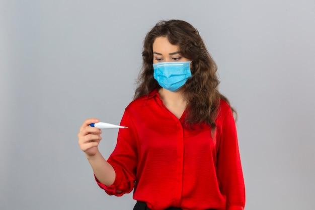 Młoda zmartwiona kobieta ubrana w czerwoną bluzkę w medycznej masce ochronnej patrząc na cyfrowy termometr w dłoni na na białym tle