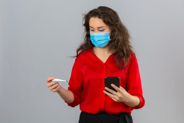 Młoda zmartwiona kobieta ubrana w czerwoną bluzkę w medycznej masce ochronnej patrząc na cyfrowy termometr w dłoni, trzymając telefon komórkowy w drugiej ręce na białym tle