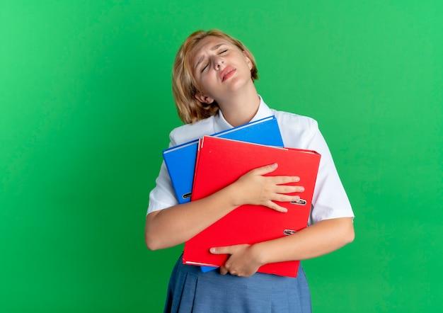 Młoda zmęczona blondynka rosyjski posiada foldery plików na białym tle na zielonym tle z miejsca na kopię