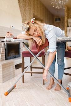 Młoda zmęczona gospodyni domowa śpi na desce do prasowania. kobieta robi prace domowe w domu. kobieta prasuje ubrania w domu