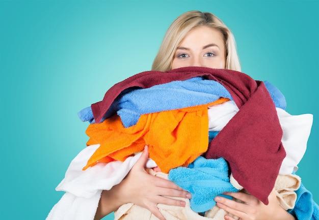Młoda zmęczona kobieta niosąca stos różnych ubrań