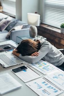 Młoda zmęczona kobieta śpi w pracy z głową na stole.