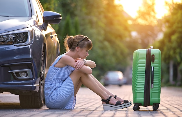 Młoda zmęczona kobieta z walizką siedzącą obok samochodu czeka na kogoś. koncepcja podróży i wakacji.
