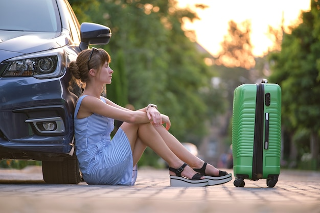 Młoda zmęczona kobieta z walizką siedzącą w pobliżu jej samochodu czeka na kogoś. koncepcja podróży i wakacji.