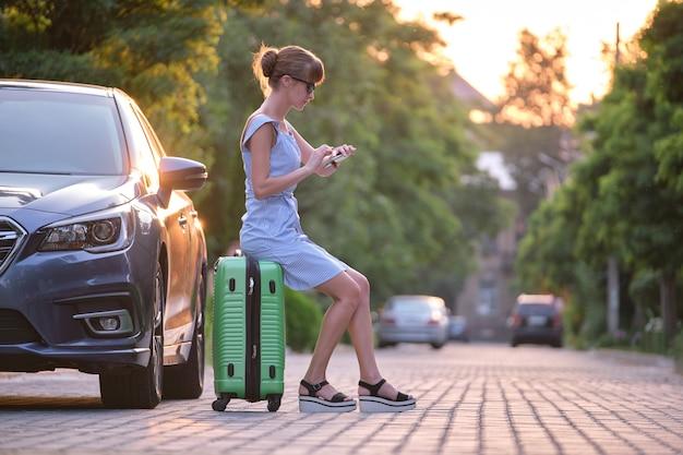Młoda zmęczona kobieta z walizką siedzi obok samochodu, czekając na kogoś. koncepcja podróży i wakacji.