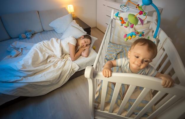 Młoda zmęczona mama zasnęła w nocy przy łóżeczku dziecka