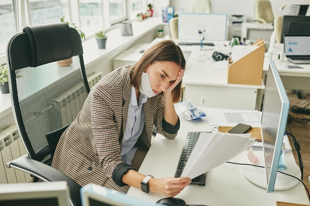 Młoda zmęczona pracownica biurowa z maską ochronną pod ustami, patrząc na dokumenty, siedząc przy miejscu pracy podczas kwarantanny