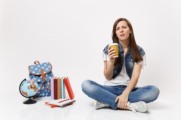 Młoda zmęczona, wyczerpana studentka trzymająca papierowy kubek z kawą lub herbatą, siedząca w pobliżu kuli ziemskiej, plecaka, podręczników szkolnych na białym tle