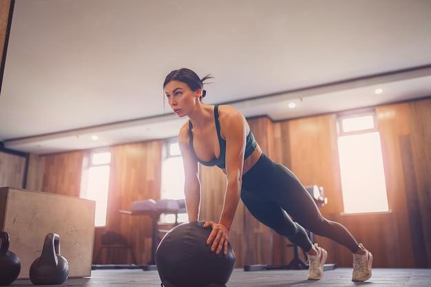 Młoda zmotywowana dziewczyna robi ćwiczenia deski na piłkę na siłowni