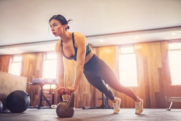 Młoda zmotywowana dziewczyna robi ćwiczenia deski przy użyciu kettlebells