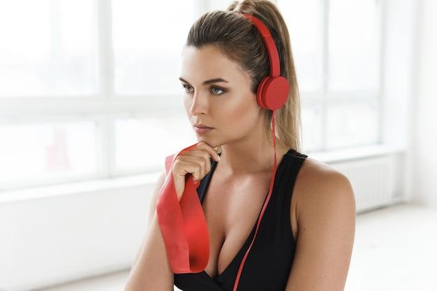 Młoda zmotywowana kobieta słucha muzyki podczas treningu z pętlą oporową
