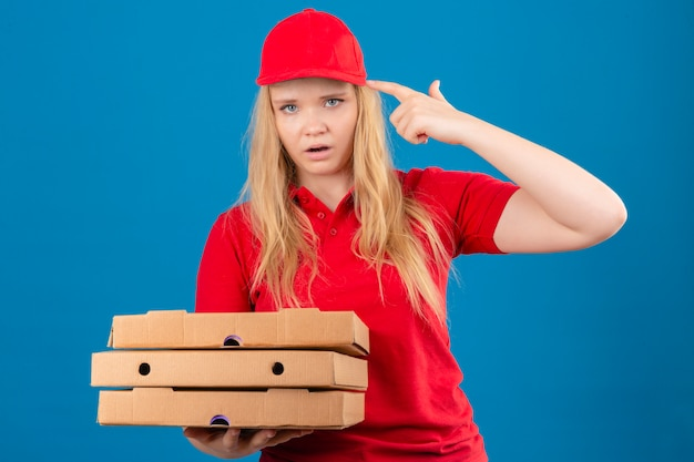 Młoda znudzona kobieta dostawy na sobie czerwoną koszulkę polo i czapkę stojącą z pudełkami po pizzy, strzelając do siebie, robiąc palec z pistoletu podpisując na odosobnionej niebieskiej ścianie