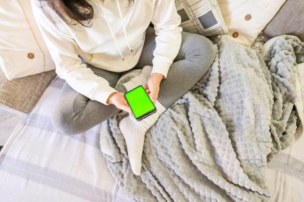 Młoda znudzona kobieta siedzi na kanapie ze skrzyżowanymi nogami za pomocą smartfona z zielonym ekranem. nowa technologia wi-fi powoduje, że cały dzień tracisz czas w internecie. spędzanie czasu w sieci społecznościowej