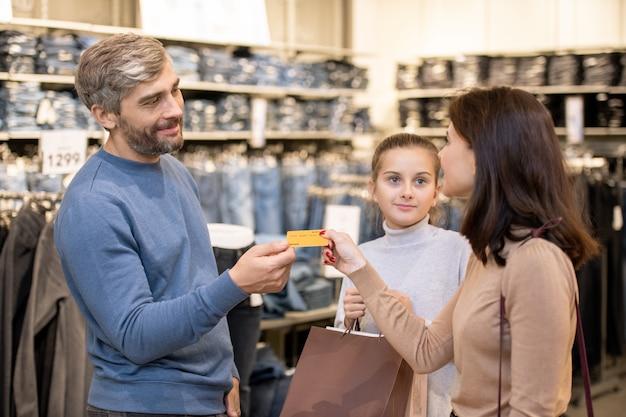 Młoda żona daje mężowi plastikową kartę, aby zapłacić za zakup, podczas gdy ich córka trzyma papierowe torby w dziale odzieży codziennej