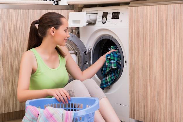 Młoda żona kobieta pranie ubrań w pobliżu maszyny