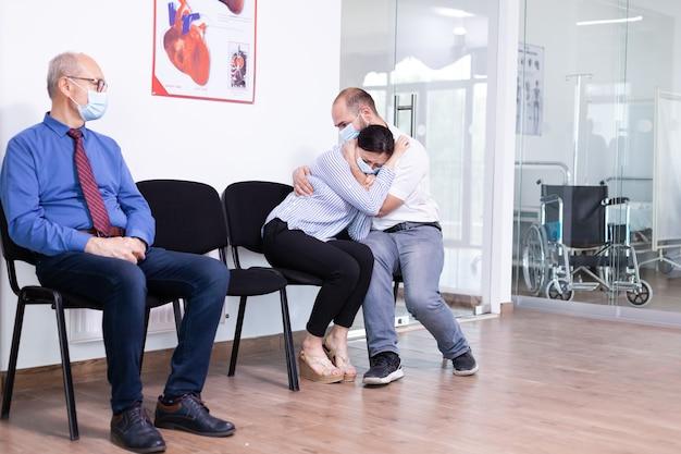 Młoda żona płacze po wysłuchaniu złych wiadomości od lekarza w szpitalnej poczekalni