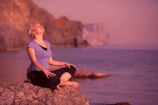 Młoda zrelaksowana kaukaska kobieta siedzi na kamieniu i cieszy się promieniami letniego słońca na tle morza podczas długo wyczekiwanych wakacji w letni dzień. koncepcja odpoczynku i regeneracji