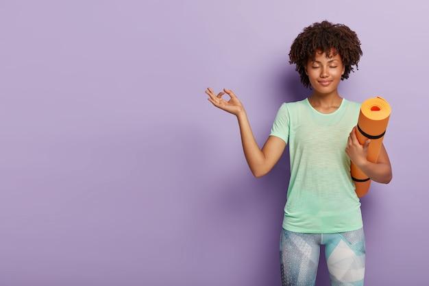 Młoda zrelaksowana kobieta ćwiczy jogę z karematem