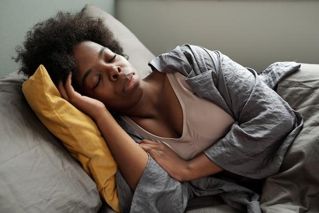 Młoda zrelaksowana kobieta pochodzenia afrykańskiego śpiąca w łóżku
