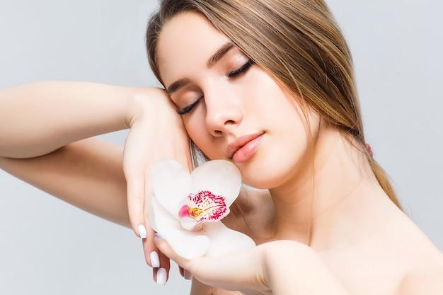 Młoda zrelaksowana półnaga dama z zamkniętymi oczami, stojąca na białym tle z kwiatem na rękach