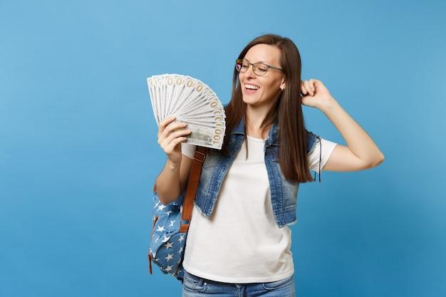 Młoda zrelaksowana roześmiana studentka w okularach z plecakiem trzymająca rękę na włosach trzymająca pakiet wiele dolarów, gotówka na białym tle na niebieskim tle. edukacja w liceum ogólnokształcącym.