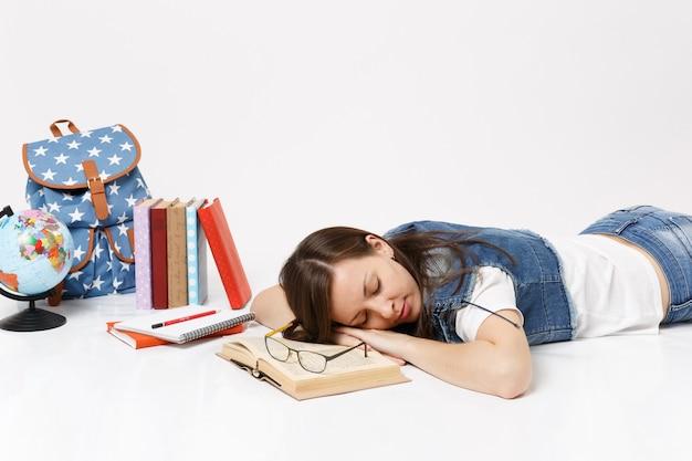 Młoda zrelaksowana zmęczona studentka w dżinsowych ubraniach odpoczywająca śpi na książce leżącej w pobliżu globu, plecaka, podręczników szkolnych na białym tle