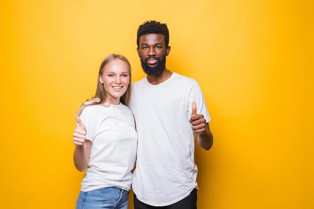 Młoda zróżnicowana para z kciukami do góry odizolowana na żółtej ścianie