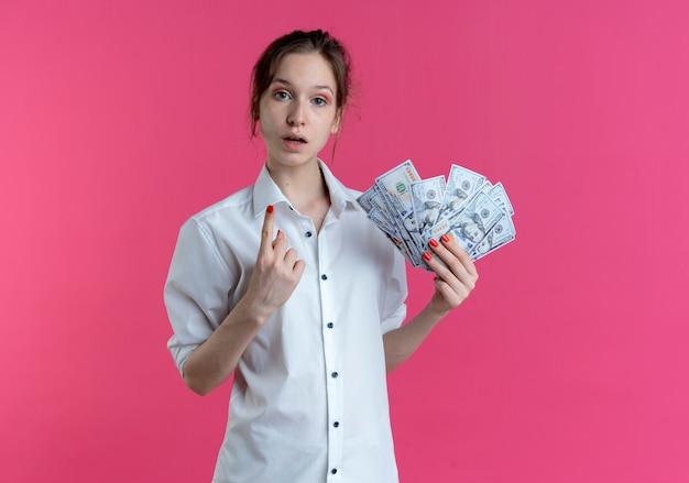 Młoda zszokowana blondynka rosjanka wskazuje na trzymanie pieniędzy na białym tle na różowej przestrzeni z miejsca na kopię