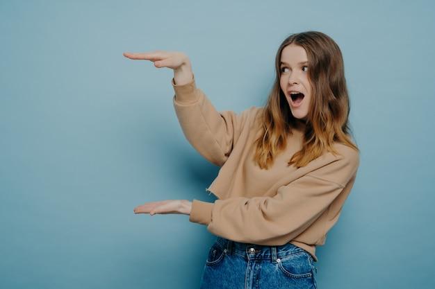 """Młoda zszokowana brunetka kobieta w beżowym swetrze pokazująca duży duży rozmiar rękami i wyrażająca wyraz """"wow"""", stojąc na jasnoniebieskim tle. koncepcja promocji i reklamy"""