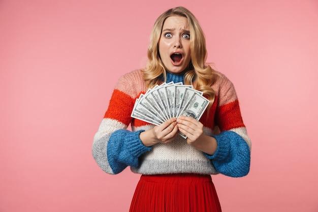 Młoda zszokowana, całkiem piękna kobieta pozuje na białym tle nad różową ścianą trzymającą pieniądze