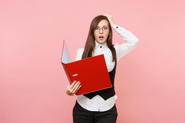 Młoda zszokowana kobieta biznesu w okularach trzymając czerwony folder na dokumenty dokument przywiązanie do głowy na białym tle na pastelowym różowym tle. szefowa. osiągnięcie bogactwa kariery. skopiuj miejsce na reklamę.