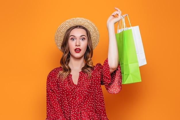 Młoda zszokowana kobieta w czerwonej letniej sukience i słomkowym kapeluszu, trzymając w rękach pakiety zakupów na pomarańczowej ścianie. koncepcja wyprzedaży