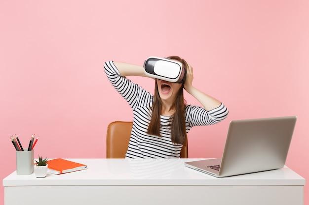 Młoda zszokowana kobieta w zestawie słuchawkowym wirtualnej rzeczywistości, trzymająca się głowy, krzycząc, usiądź i pracuj przy białym biurku z laptopem
