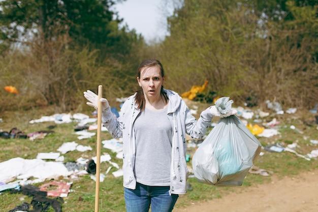 Młoda zszokowana kobieta w zwykłych ubraniach i lateksowych rękawiczkach do czyszczenia, trzymając worki na śmieci w zaśmieconym parku