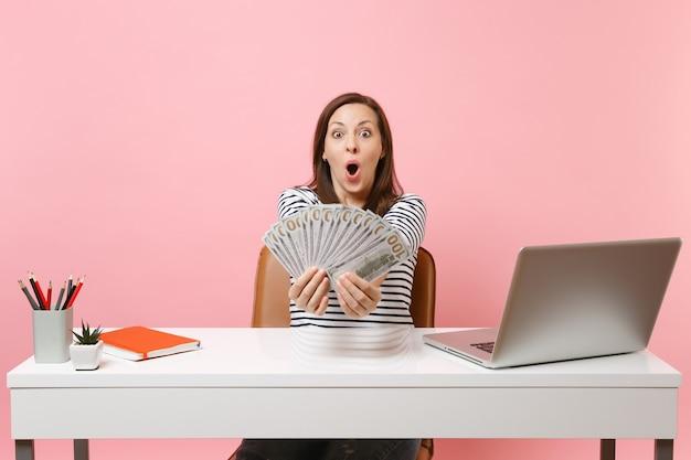 Młoda zszokowana kobieta w zwykłych ubraniach pokazujących mnóstwo dolarów, siedzące pieniądze w gotówce, pracujące przy białym biurku z laptopem na pc pc