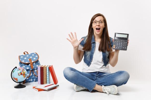 Młoda zszokowana podekscytowana studentka trzymająca kalkulator rozkładający ręce, ucząca się matematyki, siedząca w pobliżu kuli ziemskiej, plecaka, podręczników szkolnych na białym tle