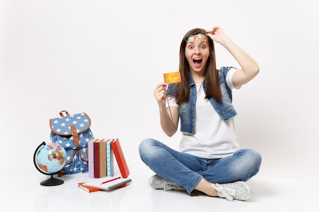 Młoda zszokowana podekscytowana studentka z otwartymi ustami usuwająca okulary trzymająca kartę kredytową w pobliżu kuli ziemskiej, plecaka, podręczników szkolnych na białym tle