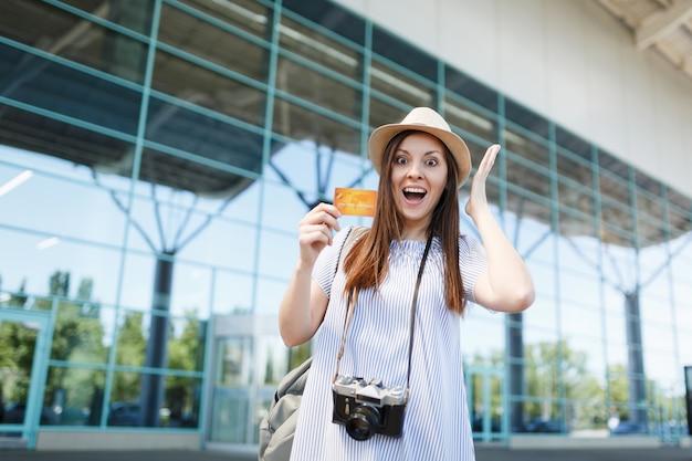 Młoda zszokowana podróżniczka turystyczna kobieta z retro vintage aparatem fotograficznym, rozkładająca ręce, trzymająca kartę kredytową na międzynarodowym lotnisku