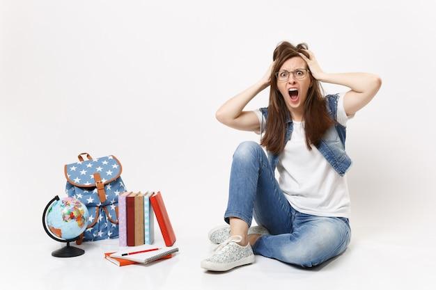 Młoda zszokowana przerażona studentka w dżinsowych ubraniach krzyczy, trzymając się głowy, siedzi w pobliżu kuli ziemskiej, plecak szkolnych podręczników na białym tle