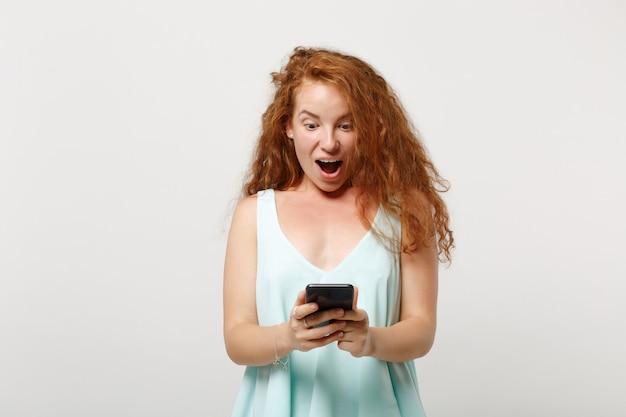 Młoda zszokowana ruda kobieta dziewczyna w dorywczo lekkie ubrania pozowanie na białym tle na białym tle, portret studio. koncepcja życia ludzi. makieta miejsca na kopię. używając telefonu komórkowego, wpisując wiadomość sms.