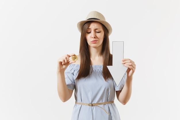 Młoda zszokowana smutna kobieta trzyma bitcoin, monetę złotego koloru, strzałkę spadku wartości w dół na białym tle. finanse i biznes, koncepcja wirtualnej waluty online. powierzchnia reklamowa. skopiuj miejsce.