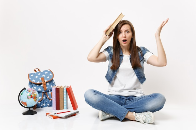Młoda zszokowana studentka w dżinsowych ubraniach trzymająca książkę w pobliżu głowy rozkładająca rękę siedzącą w pobliżu kuli ziemskiej, plecaka, podręczników szkolnych na białym tle