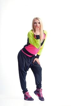 Młoda zszokowana tancerka w sportowym stroju pozuje zaskoczona zakrywając usta ręką odizolowaną