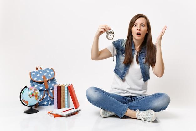 Młoda zszokowana zirytowana studentka trzymająca budzik rozkładający ręce siedząca w pobliżu kuli ziemskiej, plecaka, podręczników szkolnych na białym tle