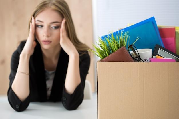 Młoda zwolniona pracownica siedząca obok pudełka z rzeczami w biurze, nie wiedząc, co robić dalej. wywalanie koncepcji.