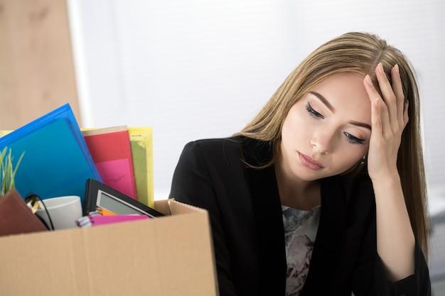 Młoda zwolniona pracownica w biurze siedząca obok kartonu z rzeczami. wywalanie koncepcji.